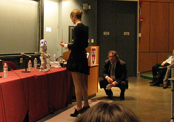 Fem and bot: Heather Knight faces her 'Star Wars'-performing robot, while H+ chairman David Orban looks on, kneeling.